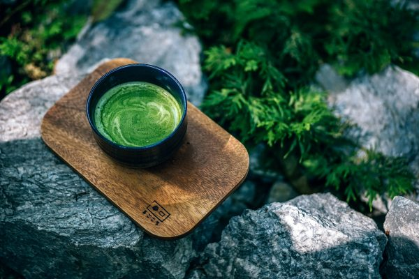 green tea incup on rocks